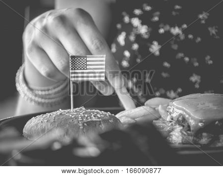 Female hand picks hamburger potatoes with USA flag monochrome