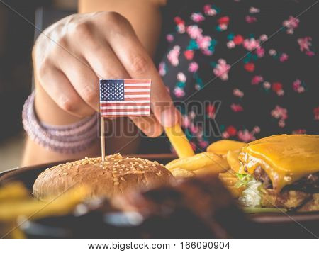 Female hand picks hamburger potatoes with USA flag