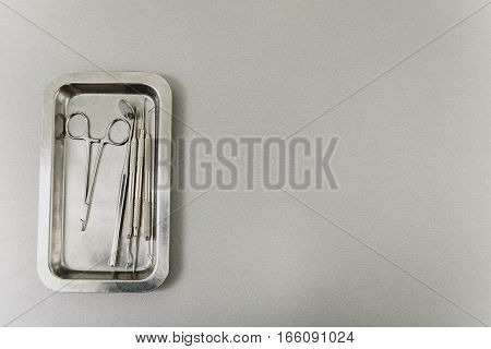 on grey background dental scissors, angled mirror and medical explorers. Copy space in right side