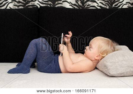 Little cute girl is playing with a smartphone, touching the screen, lying on the sofa