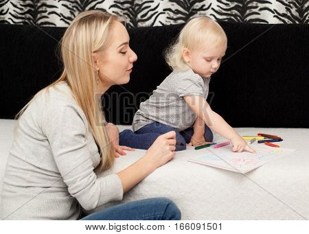 Young happy couple - mother and the daughter are playing together, drawing with the pencils