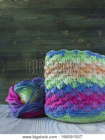 Pink violet magenta white and green bag and yarn ball. Cotton yarn for knitting crochet. The beginning of the bright bag