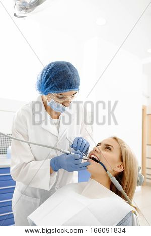 Odontologist stopping set of cavities in mouth of woman. Stomatologist standing near cooling patient
