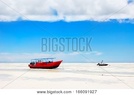 Red boat on the beach of Zanzibar on the blue sky background. Africa. Tanzania.