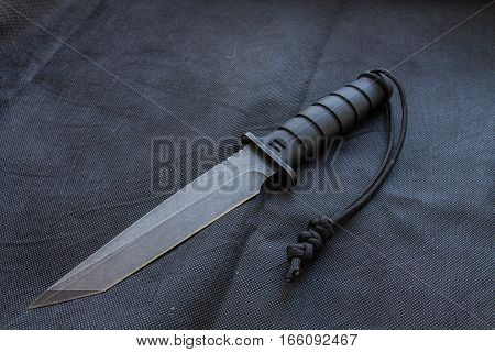 Black knife on a black background for the military. Tactical knife with lanyard.