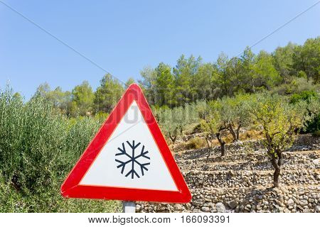 Warning road sign coldsnow caution at time and in area looks misplaced surrounded by almond groves Spain