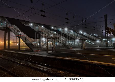 A few stairs lead to the train platforms on the overpass. Burning lights. Night time.
