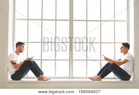 Cheerful male friends are resting near window with mobile phones. They are looking at each other and laughing