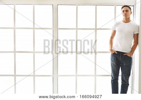 Confident young man is posing near window. He is putting hands in pockets and looking at camera with serenity. Copy space in left side