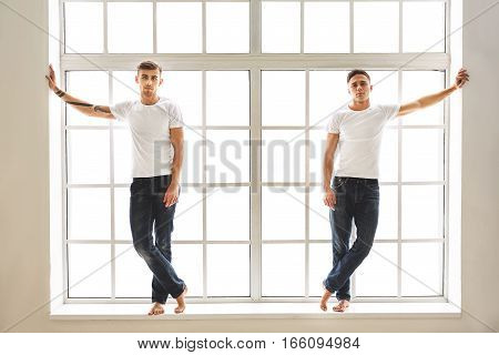 Two pensive men are standing on windowsill barefoot. They are leaning arms on walls and looking at camera with assurance