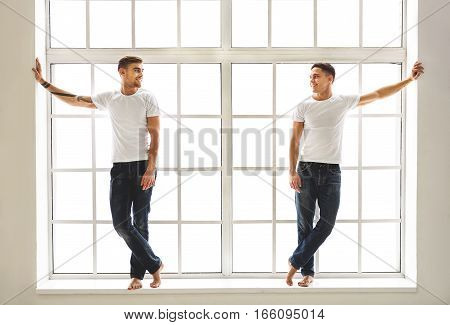 Joyful young male friends are talking and laughing. They are standing on near window while leaning hands on walls