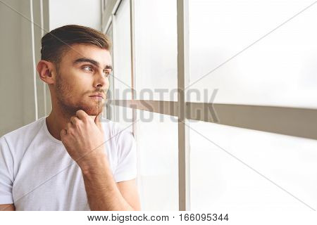 Young man is making serious decision. He is standing and looking at window with concentration