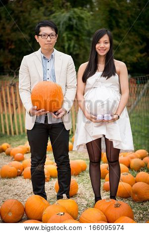 Couple maternity photo with pumpkin in pumpkin patch