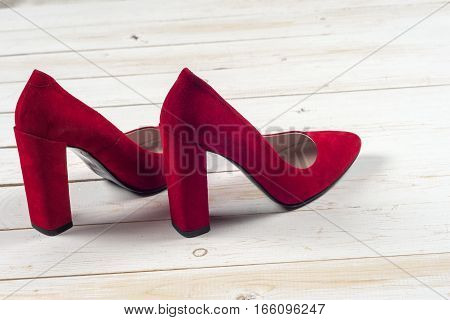 Red female shoes on high heels isolated on white wooden background