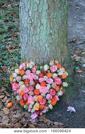 Heart Shaped sympathy or funeral flowers near a tree at a cemetery