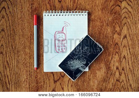 Freehand drawing of old phone in notebook. Smartphone with broken screen on wooden table. Dream visualization desire need a new phone concept