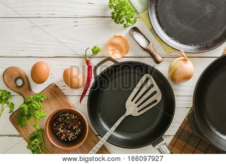 Morning breakfast. Cooking eggs. Frying pan and ingredients: onions, garlic, parsley, spices and salt. Space for text. View from above