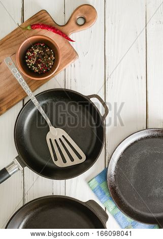 Several empty cast-iron frying pans on a white wooden background. View from above. mix peppers in a bowl.
