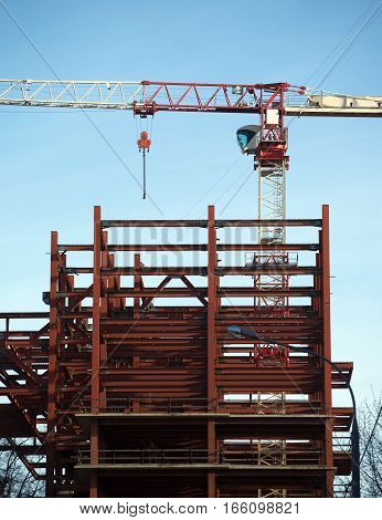 Hoisting tower crane in construction process on top of construction modern building frame over blue sky closeup