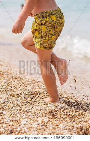 Little feet on the beach of small stones near the sea