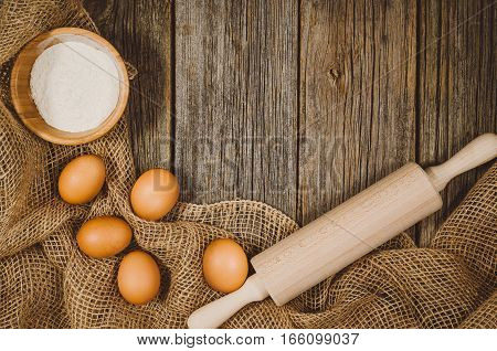 Baking or cooking ingredients background. Top view photograph with kitchen utensils on vintage, natural, raw, wooden background with visible texture.