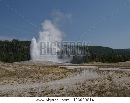 Old Faithful in Yellowstone National Park nears the end of its eruption cycle on a sunny summer day.