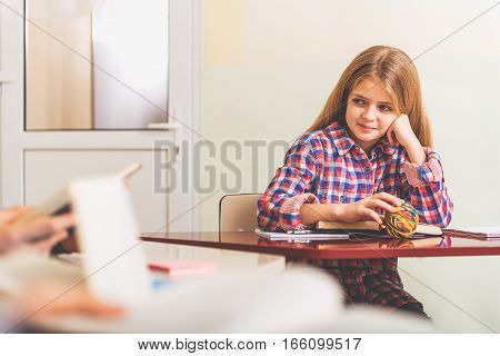 Cute girl is sitting at red polished desk with open volume. She looking aside with light smile