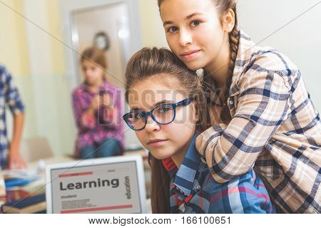 Curious girls are near open laptop in classroom. One teenager incline onto shoulders of other. They looking at camera