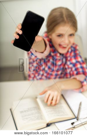 Female teenager is sitting at table and showing mobile with happy smile. Focus on phone