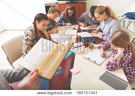 It is time to study. Attentive children are sitting near working desks. They absorbedly writing in their notebooks