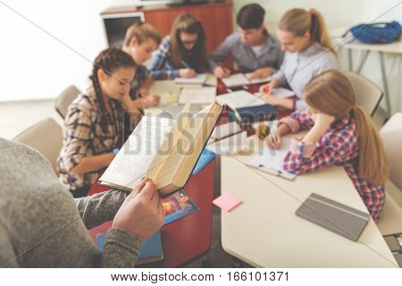 Concentrated pupils are sitting around common desk. They noting information. Focus on open book in hands of teacher