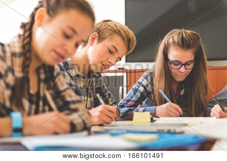 Attentive teenagers are sitting around table and absorbedly writing information