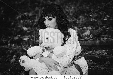 Young Sad Lonely Brunette Girl At Sleepwear With Soft Toy Bear On Hands. Black And White Photo.