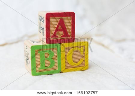 Wooden Alphabet Blocks On Quilt Spelling Abc Stacked