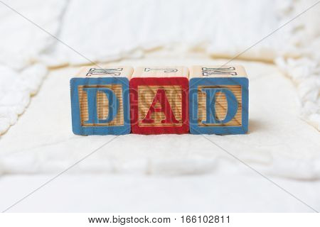 Wooden Alphabet Blocks On Quilt Spelling Dad