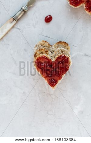 Close-up of Heart Shaped Toast with Strawberry Jam on Marble Table