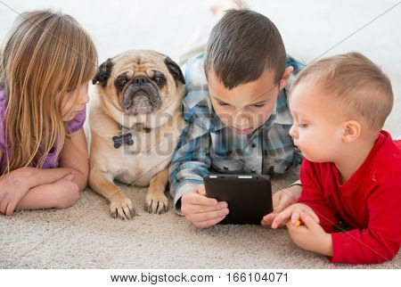 Young children playing games with computer tablet.