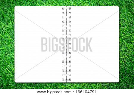 Open notebook paper on green grass background for design with copy space for text or image.