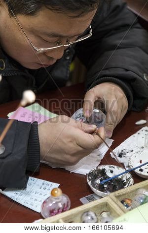 Beijing, China - January 3, 2017: Chinese artist painting the inside of a glass container. This is a specific skill and uses an angled brush.
