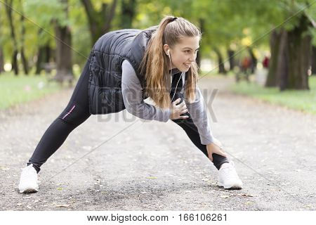 Beautiful young woman running in the park Selective focus and small depth of field lens flare