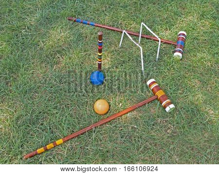 This game of croquet, which dates back to the mid-1856's, is over, its balls, mallets, wickets and stake left on the grassy lawn.