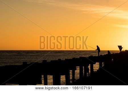 People fishing of Whanganui old wharf at sunset.