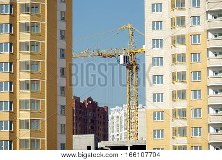 Hoisting tower crane in construction new apartment building process inside residential district