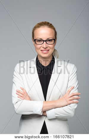 Portrait of cheerful, beautiful, smart, young businesswoman in white business attire, wearing black eyeglasses, standing with arms crossed against gray background. Copy space on top.
