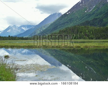 Beautiful summer landscape with hills and clouds reflecting on the surface of the water at the lake. Day hike in Alaska with mountains mirrored in the pond.
