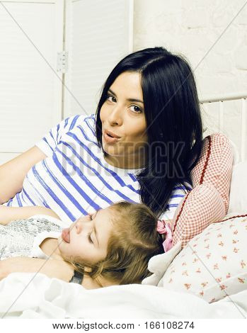 portrait of happy real mother and her daughter playing in bad, lifestyle people concept close up