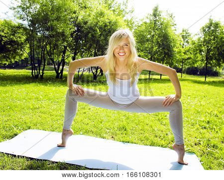 blonde real girl doing yoga in green park, lifestyle people concept close up