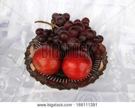 Fruits on silver dish on the fabric background