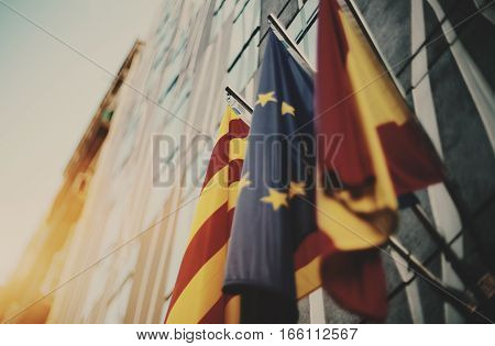 True tilt shift shooting of three waving flags on modern business office facade in Barcelona: European Union Catalonia Spain sunny summer day with clean teal sky