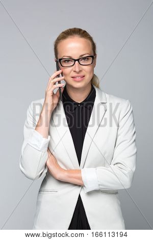 Portrait of beautiful young caucasian businesswoman wearing black blouse and white business attire, talking on mobile phone. Studio portrait shot on grey background.